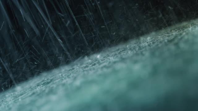 vidéos et rushes de super ralenti et gros plan d'un verre de voiture pendant qu'il pleut, les essuie-glaces sont en levant l'eau de celui-ci. - pare brise