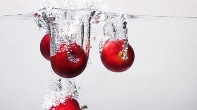 Super slow motion: Apple drop into fresh water on white background