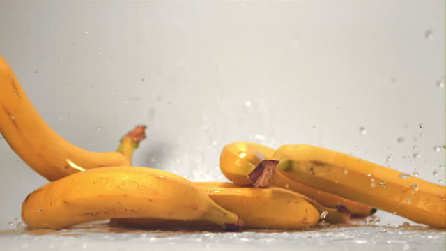 Super slow motion bananas on a white background fall on a table with splashes. Filmed on a high-speed camera at 1000 fps.