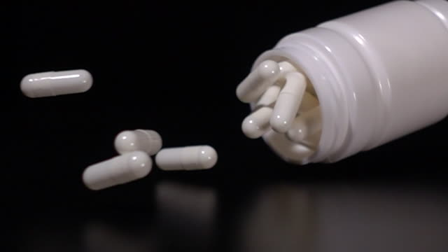 Super slow motion: Bottle capsule falling on black background Super slow motion and close up shot of Bottle white capsule falling on black background with reflection. Medicine and medication concept on clean background pill bottle stock videos & royalty-free footage