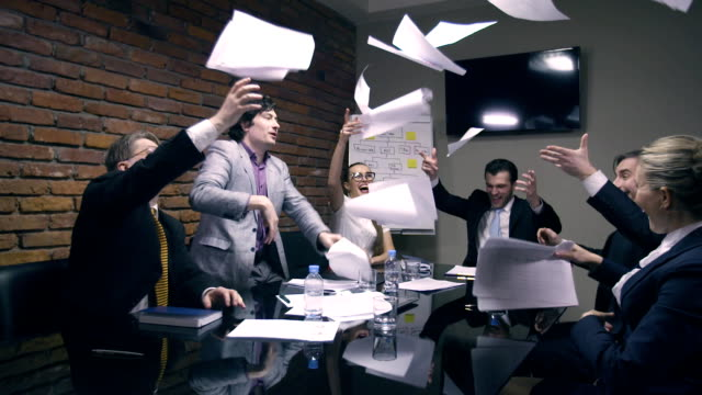 Super slow motion. Business people throw papers into air video