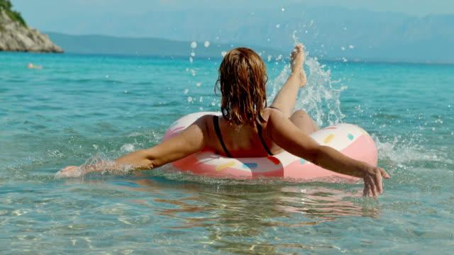 stockvideo's en b-roll-footage met ms super slow motion zorgeloos vrouw spetteren in opblaasbare ring op zonnige zomer oceaan, peljesac, kroatië - opblaasband