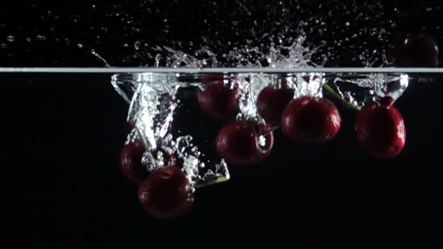 Super slow motion: Cherry drop into fresh water on black background
