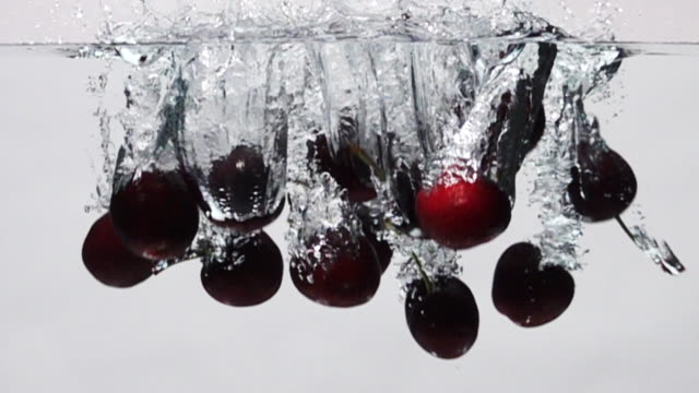 Super slow motion: Cherry drop into fresh water on white background