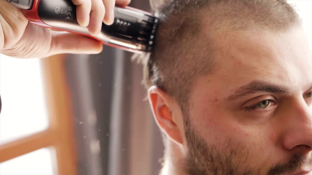 super slow motion close up shot of man preparing for army getting his hair cut - testa video stock e b–roll