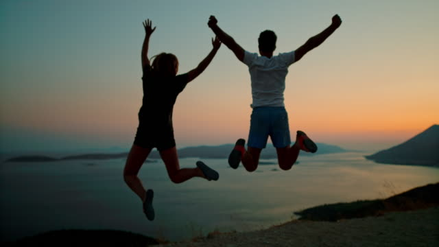 MS Super slow motion couple jumping for joy at scenic ocean overlook at dusk,Peljesac,Croatia