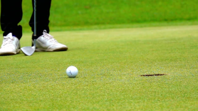 Super slow motion Golfer putting ball to hole to the winner in beautiful golf course video