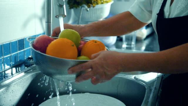 Super Slow motion : Hands washing fruits close up.