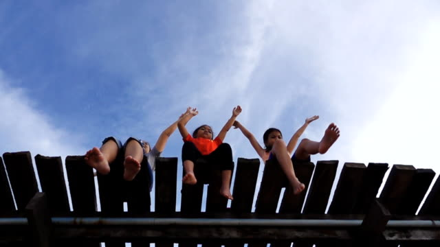 HD Super Slow motion: Happy Family, Mother and her daughter sitting Feet hanging off pier over the sea