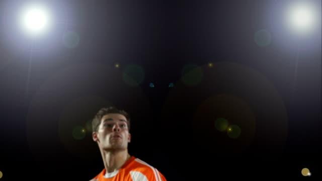 vídeos de stock e filmes b-roll de super câmara lenta, posição futebol bola sob floodlights - liga desportiva