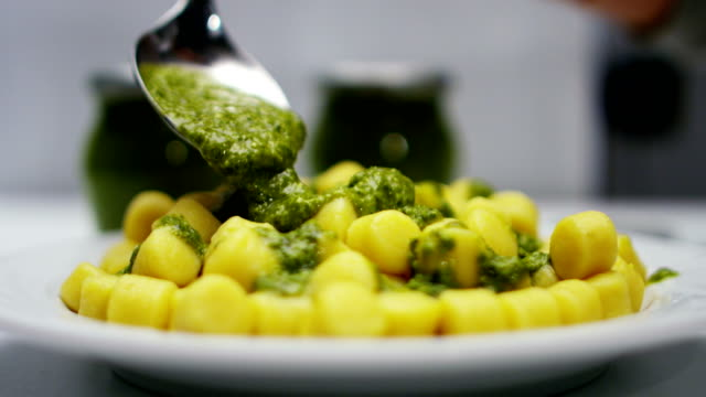 super slow motion macro of serving gnocchi with pesto sauce on the dish (close up)super slow motion macro of serving gnocchi with pesto sauce on the dish (close up) - pinolo video stock e b–roll