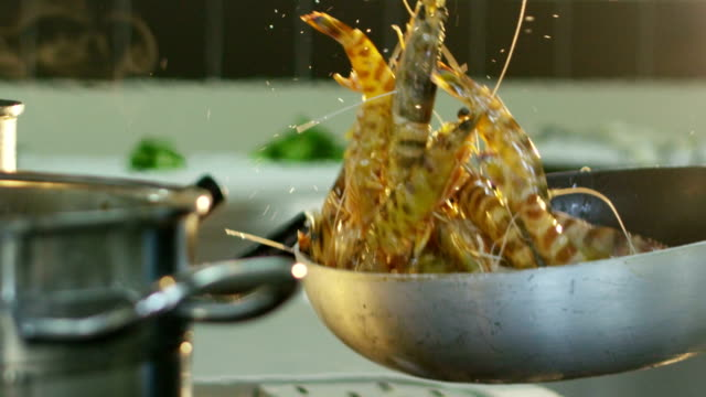 Super slow motion macro of shrimps flipping with a pan (close up)