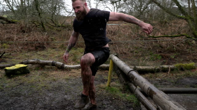 Super Slow Motion: Male Jumping from water in Mud Run Assault Course / Obstacle Course Stock HD video clip footage of a man jumping out from the water over a beam during a mud run. He is racing through this assault course / obstacle course and determined to win. Filmed in Super Slow Motion. mud stock videos & royalty-free footage