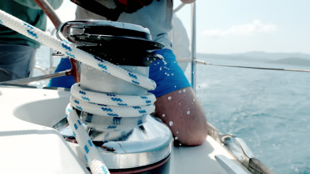 CU Super slow motion man adjusting rigging on sailboat Super slow motion man adjusting rigging on sailboat. CU,slow motion. yachting stock videos & royalty-free footage