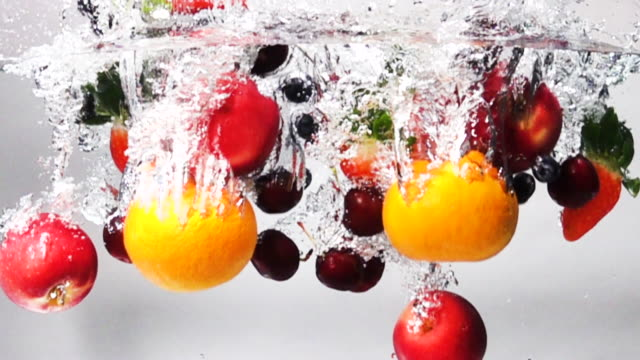Super slow motion: Mix Fruit drop into fresh water on white background