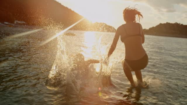 stockvideo's en b-roll-footage met ms super slow motion moeder en dochter springen in zonnige, idyllische oceaan bij zonsondergang, peljesac, kroatië - woman water