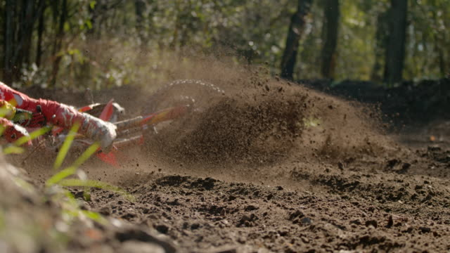 MS Super slow motion motocross racer sliding, falling off bike on dirt course