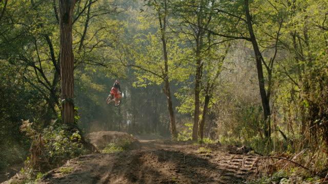 ms super slow motion motocross ryttare hoppar över solig smuts kurs i skogen - skatepark bildbanksvideor och videomaterial från bakom kulisserna