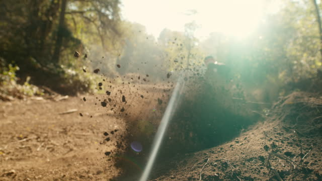 MS Super slow motion motocross rider speeding along sunny course, kicking up dirt