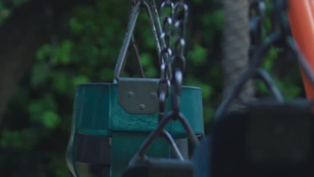 super zeitlupe von leeren schaukeln auf einem spielplatz - kinderspielplatz stock-videos und b-roll-filmmaterial