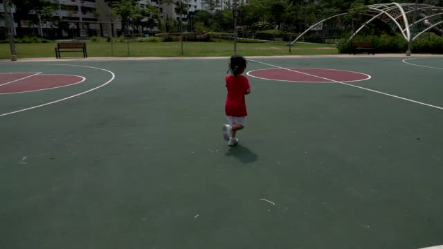Super Slow Motion shot of a little girl running in the outdoor basketball court Super Slow Motion shot of a little girl running in the outdoor basketball court. Rear-view tracking shot. one girl only stock videos & royalty-free footage