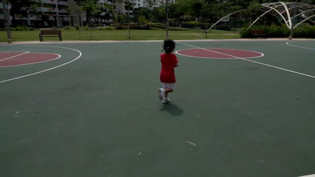сверхскоростная съёмка фото маленькая девочка, бег на открытом воздухе в баскетбольной площадке - только одна девочка стоковые видео и кадры b-roll