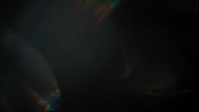 super slow motion shot of abstract bokeh light moving real organic light leaks, rainbows and orbs made with a set of vintage film lenses. a seamlessly looped, beautiful overlays or backgrounds for editing - use them in add or screen mode on any nle - утечка света стоковые видео и кадры b-roll