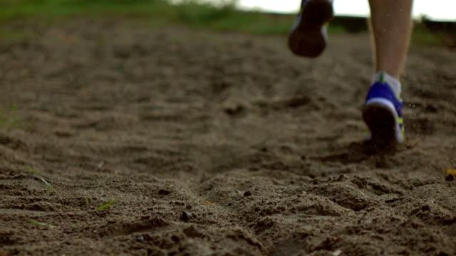 Super slow motion steadicam shot of blurred runner's legs and flying dirt. Sandy riverside, telephoto lens video