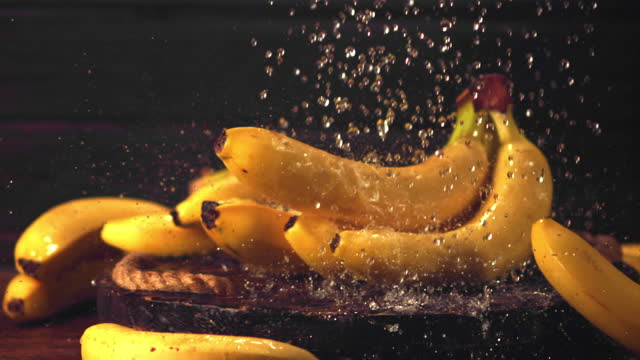 Super slow motion water falls on bananas. Filmed on a high-speed camera at 1000 fps.