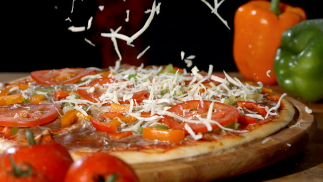 hd super slow-mo: adding a sprinkle of cheese on pizza - 食品 個影片檔及 b 捲影像