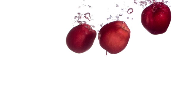 HD Super Slow-Mo: Apples Splashing Into Water video