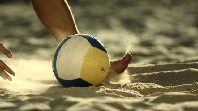 HD Super Slow-Mo: Beach Volleyball Player Picking Up A Ball HD1080p: Low Angle Super Slow Motion shot of an unrecognizable beach volleyball player picking up a ball while sliding barefoot on a beach and kicking sand up. Recorded at 1050 fps volleyball sport stock videos & royalty-free footage