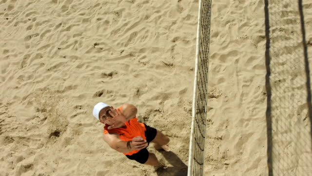 hd super slow-mo: beach volleyball player serving - volleyball stock videos and b-roll footage