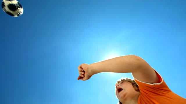 hd 超スローモーション: ヘディングをする少年 - スポーツ用品点の映像素材/bロール