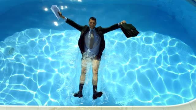 hd super slow-mo: businessman falling into swimming pool - kille hoppar bildbanksvideor och videomaterial från bakom kulisserna