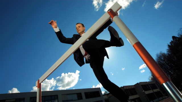 HD Super Slow-Mo: Businessman Jumping Over A Hurdle video