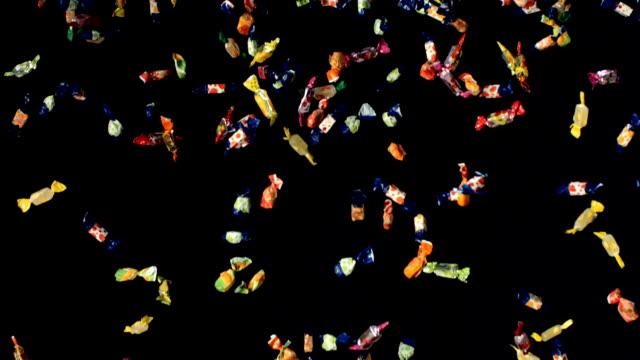 super zeitlupe, hd: süßigkeiten fallen auf schwarzem hintergrund - scheibe portion stock-videos und b-roll-filmmaterial