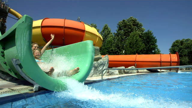 hd super slow-mo: cheerful mother and daughter in water park - vattenrutschbana rutschkana bildbanksvideor och videomaterial från bakom kulisserna