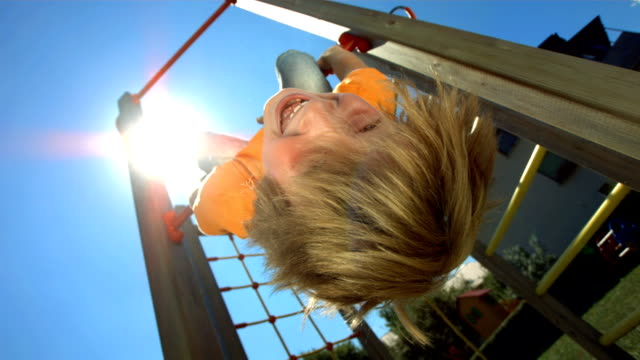 HD Super Slow-Mo: Child Hanging From Jungle Gym video