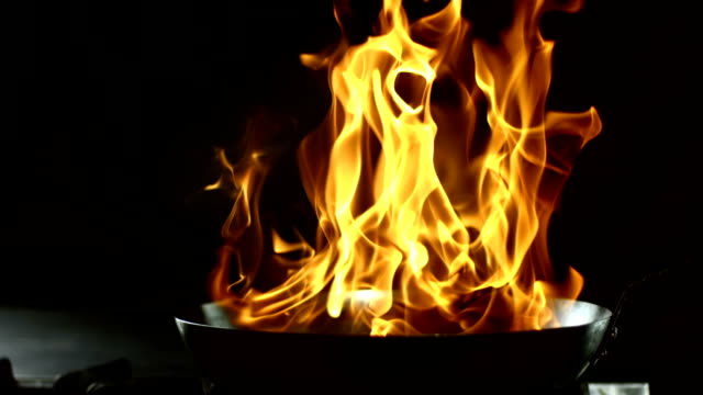 HD Super Slow-Mo: Flambeing HD1080p: Super Slow Motion shot of a burst of flames coming from a pan while flambeing food on the stovetop. commercial kitchen stock videos & royalty-free footage