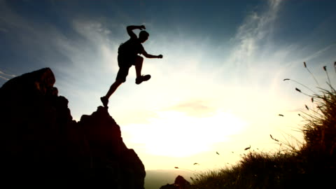 HD Super Slow-Mo: Hiker Jumping From A Rock HD1080p: Super Slow Motion shot of a hiker jumping from a rock at sunset. Recorded at 1050 fps. freedom stock videos & royalty-free footage