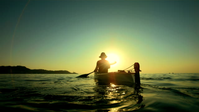 hd super slow-mo: kayaking toward the sunset horizon - kanotsport bildbanksvideor och videomaterial från bakom kulisserna