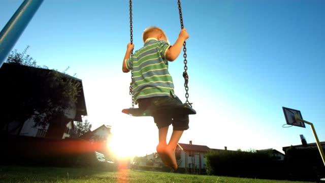 hd super slow-motion: ragazzino fiore contro il cielo soleggiato - oscillare video stock e b–roll