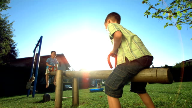 HD Super Slow-Mo: Little Boys Playing On A Seesaw video