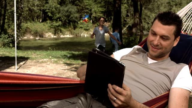 HD Super Slow-Mo: Man Using A Digital Tablet In Hammock video