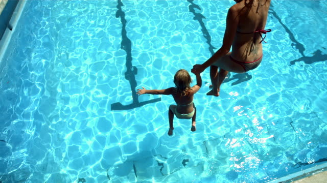 HD Super Slow-Mo: Mother And Daughter Jumping Into The Pool video
