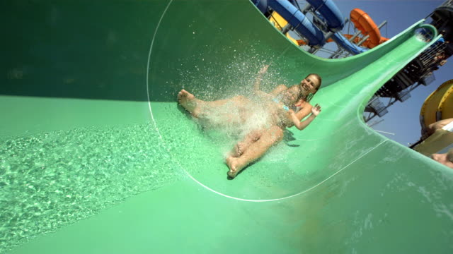 hd super slow-mo: mother and daughter sliding on water slide - vattenrutschbana rutschkana bildbanksvideor och videomaterial från bakom kulisserna