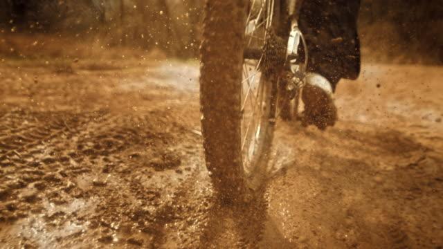 スーパースローモー: カメラで泥を蹴る mtb バイカー - 動物に乗る点の映像素材/bロール