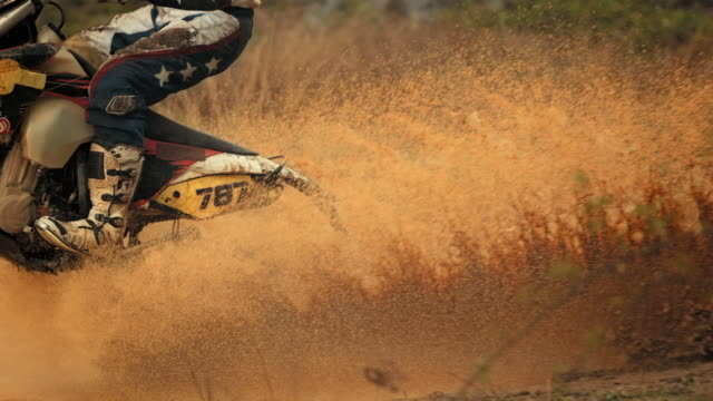 super slow-mo: mx rider riding through mud - motocross video stock e b–roll