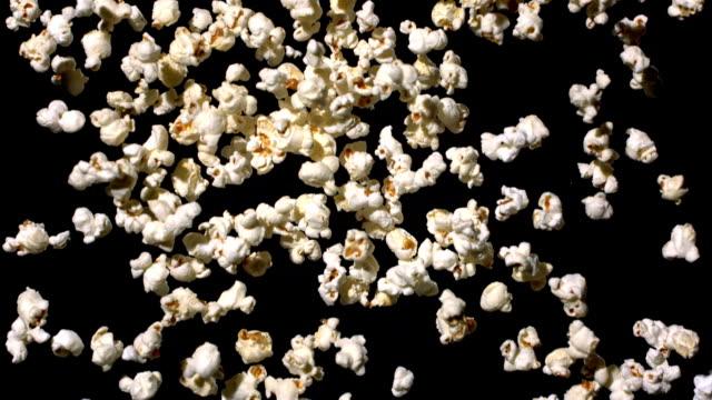 stockvideo's en b-roll-footage met hd super slow-mo: popcorn falling over black background - popcorn